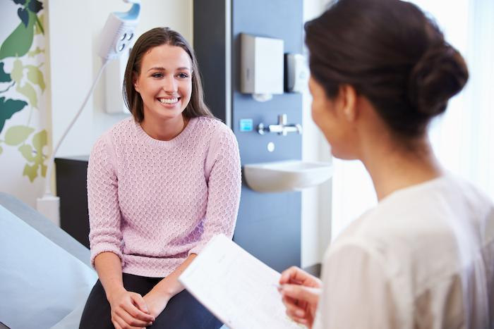 Doctor talking with a smiling female patient