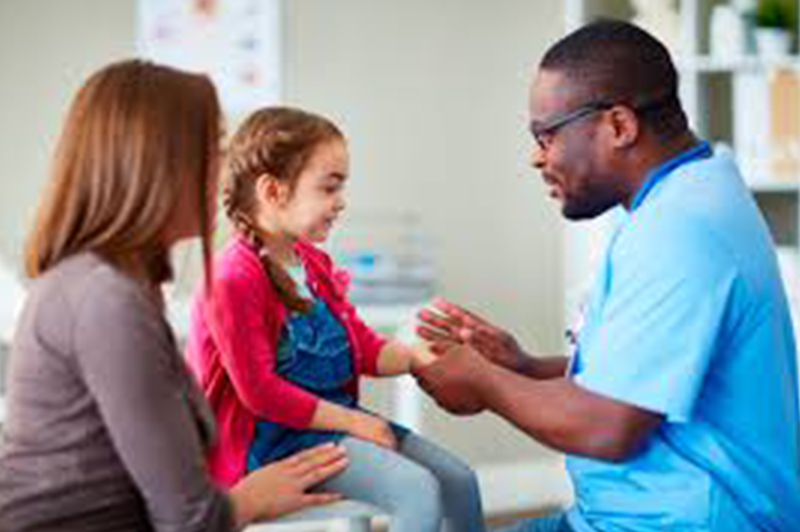Pediatrician examining a young female patient