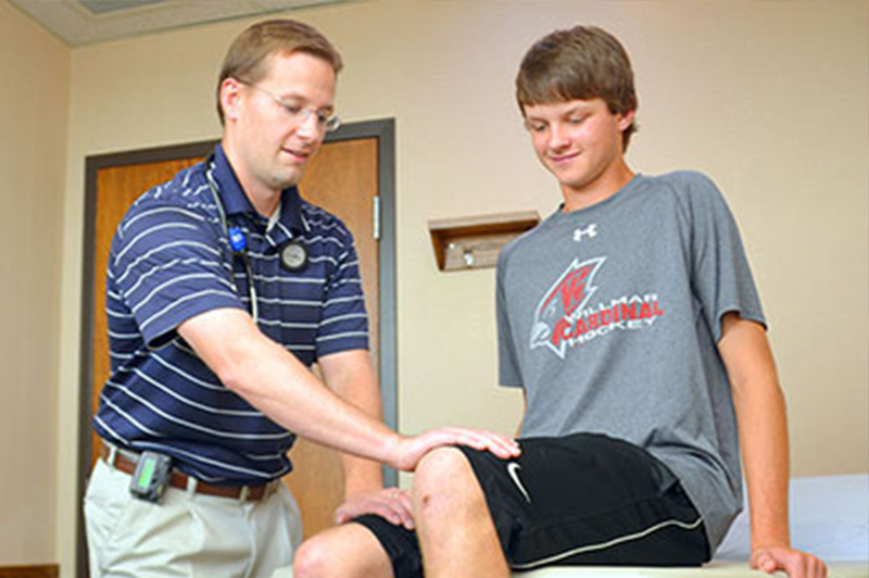 Sport therapist checking the knee of a patient